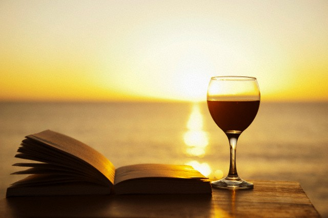 Glass of wine and book on table outdoors